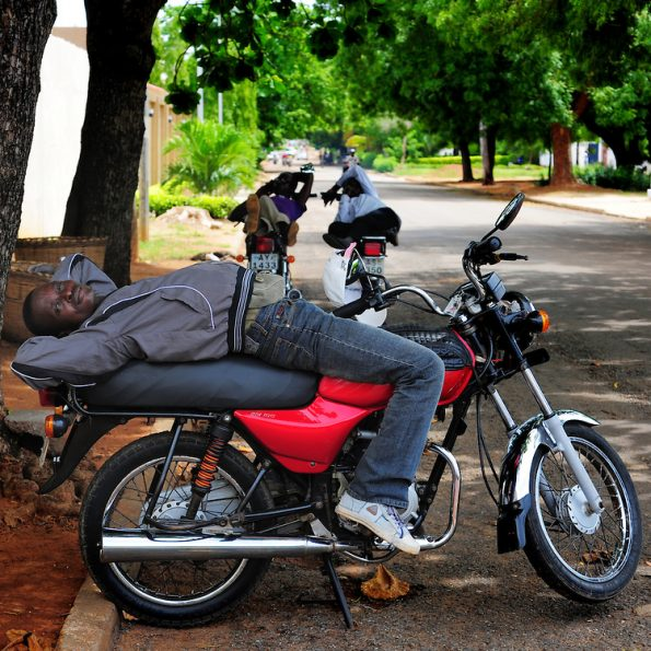 12-05-29 - LOME, TOGO - Zemidjan ('take me quickly' in Fon) driver Eric Pidjolo demonstrates how he sleeps on his motorcycle in LomŽ, Togo on May 29. Underpaid, rarely thanked and working all hours to make a meagre living, they find very few moments of calm and quiet in their lives. And so, the moto-taxi men have perfected various ways of calmly sleeping on their motorbike as they wait for their next customer. And so, on the move amidst the chaos and bustle of daily life, they relax and sleep. Photo by Daniel Hayduk
