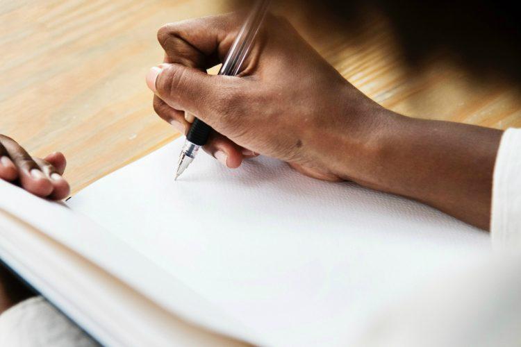 main-femme-ecrit-cahier-stylo-carnet-travail-noire-africaine